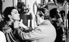 Director Luchino Visconti fixes Helmut Berger´s costume on the set of…