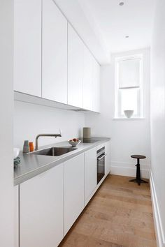 A small narrow kitchen with white units & stainless steel worktop and sink from Bulthaup. Kitchen design ideas - cabinets, taps, cupboards, sinks, lighting and wallpaper from House & Garden.