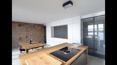 Kookeiland met een massief eiken werkblad en een ingebouwde kast van wit betonplex.
