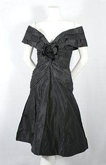 "$950  Scaasi taffeta cocktail dress, late 1950s. Although Scaasi is known as a superb colorist, he shows here that he can do the LBD with equal mastery. The effect is based on his finely honed sense of shape. Made from black silk taffeta, the only adornment is a large velvet rose at the deep ""V"" of the front neckline. With the signature off-the-shoulder neckline, draped torso and sculpted skirt, this stunner makes a sophisticated, dramatic fashion statement."