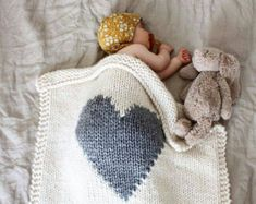 My heart baby blanket in cream with a royal blue heart (a beautiful royal blue with a hint of purple). Sweet and modern. It is the perfect size for bundling up baby in a stroller, car seat, or bassinet/cot. The grey heart blanket image is used just to demonstrate size.  This blanket will take about 6-8 weeks to knit before ready to ship. (Let me know if you absolutely must have it sooner and I will see what I can do!)  SIZE: 26 x 26 The cream yarn is 50% acrylic and 50% wool. The heart is…