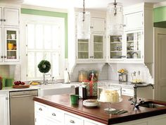 Kitchen with marble counter tops, a mahoghany-topped kitchen island, green wall color, hanging pendant lights, white cabinets, and an apron-front farmhouse sink