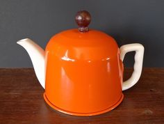 Japanese white ceramic teapot with a bright orange insulated cover.