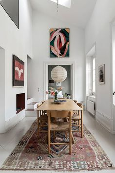 a vintage rug in a dining room adding a bohemian touch to a Scandinavian interior