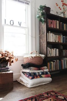 a pile of blankets with a basket full of blankets on top, so cozy! guest bedroom