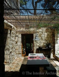 Blocks of local limestone have been used to create the impression of an old building around this covered terrace