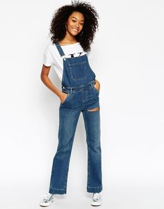 """Dungarees by ASOS Collection Mid-weight, firm-stretch denim C lip fastening to front Adjustable shoulder straps Multi-pocket design Buttoned sides Rip detailing to thigh Flared fit - cut with a straight leg that flares at the ankle Machine wash 99% Cotton, 1% Elastane Our model wears a UK 8/EU 36/US 4 and is 173cm/5'8"""" tall"""