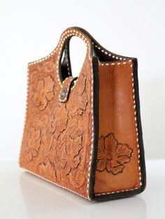 vintage western tooled leather bag From our Curator's Collection This is a vintage tooled leather handbag. The thick caramel leather bag features a western floral tooled design with silver metal lettering on the front reading Vintage Purses, Vintage Bags, Vintage Handbags, Soft Leather Handbags, Leather Purses, Tooled Leather, Leather Totes, Leather Jewelry, Leather Satchel