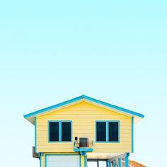 A vibrant yellow beach house with two windows like eyes against a clear aqua sky.