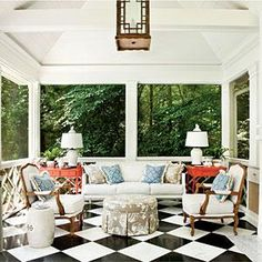 This summer house backyard retreat features a black and white checkered floor and pops of red. | #SouthernLiving.com