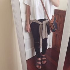 brown borks with black pants, white tshirt and tan sweater around waist