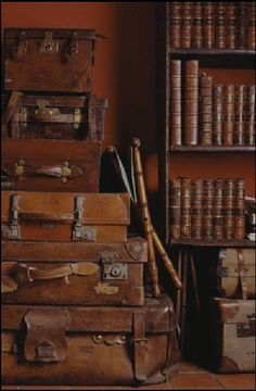 Library vignette: rust wall, a stack of cognac colored leather suitcases and shelves with leather bound books: