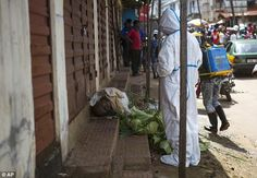 The body of an Ebola victim lies at the side of a road in a busy marketplace in Freetown, Sierra Leone after a strike by burial teams over hazard pay left corpses abandoned across the city