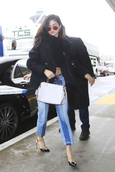 Selena Gomez rocked two-toned denim jeans, a crop top, black pumps, and red tinted sunglasses while arriving at LAX airport.