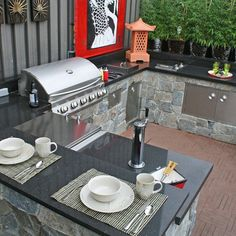 Outdoor Kitchens Designs and Ideas On The Summer : Modern Outdoor Kitchen Design Design With Stones Kitchen Table Material Also Black Granite Countertops Also Stainless Grill Appliance Also Unique Wooden Flooring Design Also Elegant White Cup Bowl Plate
