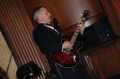 The guitarist for The John Parker Band performs on a beautiful red and black electric guitar at a wedding reception held in the historic Duquesne Club, Pittsburgh. The band dressed in black tuxedos for the elegant affair. http://www.jpband.com/weddings.html
