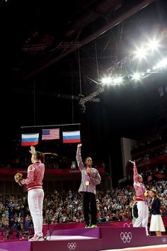 Bronze medalist Aliya Mustafina of Russia, gold medalist Gabrielle Douglas of the United States and silver medalist Victoria Komova of Russia wave during the medal ceremony in the Artistic Gymnastics Women's Individual All-Around final on Day 6 of the London 2012 Olympic Games at North Greenwich Arena on August 2, 2012 in London, England.