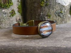 Brown genuine leather bracelet with planet Jupiter picture. The picture has been sealed with a magnifying glass dome, to protect and enhance the image.  ∞∞∞ M e a s u r e m e n t s ∞∞∞ Measures approx: • Glass dome: 16mm / 0.63 in diameter • Strap width: 1 cm / 0.4 • Total length of bracelet: select your option. If you need a length different to options, just convo me.  ∞∞∞ S i m i l a r P i e c e s ∞∞∞ You can see the entire Universe Collection here: https://www.etsy.com&...