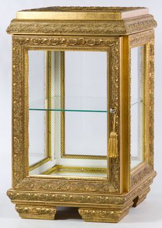 Lot 645: Table Top Display Case; Having a classical style gold painted wood frame, a glass shelf and a mirror back
