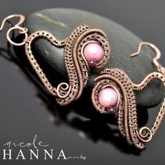 Really fun and romantic, these wire wrap earrings measure 3cm in length (excluding the ear wire), and feature a lustrous pink freshwater pearl with small garnet accent. Copper wire has been woven and coiled in an abstract, but elegant, heart shape, which hangs delicately from a copper ear wire (s...
