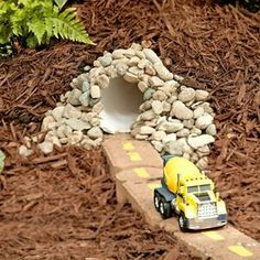 Cool outside play for boys and girls rocks, pipe, mulch, and bricks