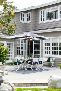 White outdoor furniture with blue cushions. This home features grey siding and white outdoor furniture with blue cushions. AGK Design Studio. Ryan Garvin Photography.