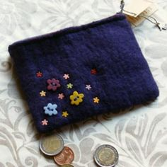 Monedero de fieltro hecho a mano a partir de lana merina, morado por fuera y malva jaspeado por dentro. Cerrado con cremallera, tiene botones y remaches con forma de flor de diferentes colores.