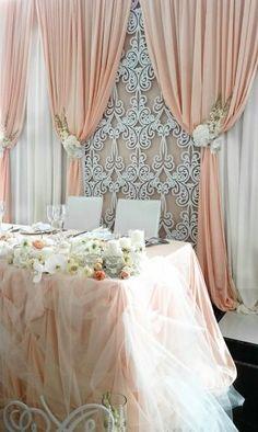 Драпированный задник за столом жениха и невесты, украшенный резной панелью и живыми цветами
