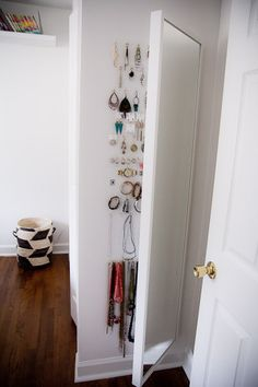 Put a wall mirror on hinges and hang jewelry behind it with small hooks. Genius! This mirror is from Ikea.