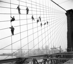 Brooklyn Bridge  Painters are suspended from wires on the Brooklyn Bridge in 1914. Check out the suits (and the one guy on top who doesn't even have shoes on!)