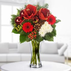 A round bouqet in red and white, made from lilies, chrysanthemums, gerbera,various greenery, and Christmas decorations.