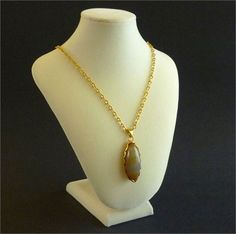 Elegant vintage blueish grey agate pendant with bands of dark grey, blue, yellow and reddish brown. The pendant comes with a 24 inch gold tone chain.   Measurements:   Pendant: Approx. 4.5 cm ( 1.77 in) x 2 cm (.77 in)   Condition: Excellent  normal vintage wear