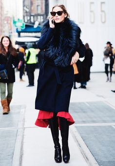 Street style look com saia vermelha, sobretudo preto e bota couro preta