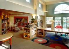Library design at Seacrest Village Assisted Living - love the stairstep bookcase, the arched window, the pretty in-bookcase lighting, the high windows to let in more light.
