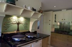 This kitchen in Gerards Cross features two splashbacks as part of an installation we did for a client. The first panel sits behind the cooker, and features a tree of life on a green background, with multicoloured leaves. At the base of the tree sits a Bearded Collie, in the field of grass that runs across the bottom of the splashback. The second splashback features similar colours that help bring the two pieces together, creating a theme that continues throughout the entire room.
