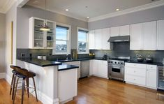 Contemporary kitchen with white cabinets black pearl granite countertops and dining peninsula