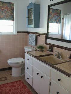 Retro bathroom. 50s bathroom, peach tile with reddish-brown trim. Blue and coral accessories.