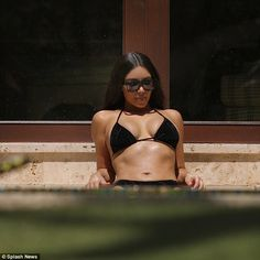 Relaxing in style: Kim Kardashian, 36, was looking better than ever as she relaxed by the poolside with her family and friends, including sister Kourtney, 37, at their private Villa Manzu in Costa Rica