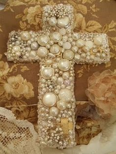 This cross is dripping with vintage pearls & jewelry. She added more chenille on the edge and antique French book pages on the back...