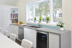 Mississauga, ON - Kitchen Renovation featuring Caesarstone Quartz countertops, built in wine fridge, white high gloss cabinets and a custom blue glass backsplash. www.atdcontractors.com