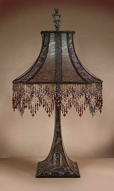 """Fansastic, cast and painted metal table lamp has vaguely Oriental scenes on each of its four sides, from the square base on up, of birds in a landscape which become fluttering leaves. The HAT shaped shade is ombre dyed from mint green into dusty cocoa-rose and then covered with metallic shot silk lace. Embroidered net in the four narrow sides and hand beaded fringe around the bottom. 31"""" high."""