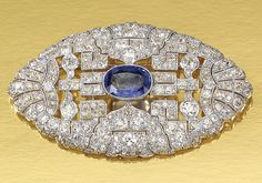 SAPPHIRE AND DIAMOND BROOCH, 1930S.  Designed as an open work plaque of geometric and fan motifs, millegrain-set with circular- and single-cut diamonds, decorated to the centre with an oval sapphire.
