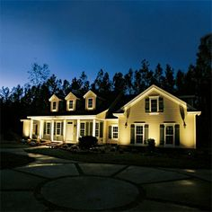Upward-facing bullet lights placed about a foot from the foundation focus attention on a house's most appealing architectural elements. Here, they are aimed at chunky porch columns, deep eaves, and dormers.