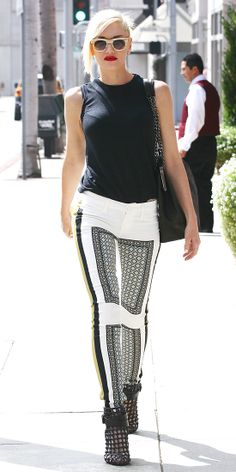 GWEN STEFANI Out and about, Gwen Stefani took to the streets in a pair of printed white pants that she styled with a sleeveless black top and caged booties.