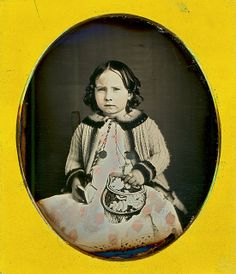 Hand tinted daguerreotype – young girl with ringlets in her hair and a white pinafore. Mid-1850s. She has an Iroquois floral bag