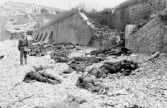 "7 January 1944:  The Royal Engineers prepare for D-Day.  The deadly result of enfilade fire during the Dieppe Raid of 1942: dead Canadian soldiers lie where they fell on ""Blue Beach"". Trapped between the beach and fortified sea wall, they made easy targets for MG 34 machineguns in a German bunker. The bunker firing slit is visible in the distance, just above the German soldier's head."