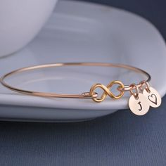 A 24k gold plated infinity symbol is the center of this bracelet. The band and charms are 14k gold filled. Each bangle is hand formed and then hammered and tumbled for shine and strength. Bangles to n