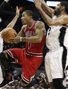 Chicago Bulls' Derrick Rose, left, goes for a layup in front of San Antonio Spurs' Tim Duncan during the second half of an NBA basketball game, Wednesday, Feb. 29, 2012, in San Antonio. Chicago won 96-89. (AP Photo/Darren Abate)