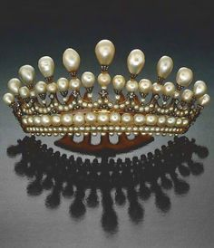 This impressive diamond and pearl tiara was brought to the Santa Monica laboratory for identification of the pearls. The tiara measures approximately 5 '/2 inches long and 2 '11 inches high (14 cm x 6.3 cm). There are a total of seven rows of pearls: five rows of round drilled pearls of various sizes, one of round and drop-shaped pearls, and a top row of all drop-shaped pearls ranging from approximately 3 mm to 10 rnin in diameter and up to 18 rnin long.