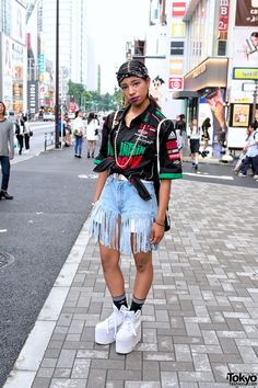 Risa is a 17-year-old girl who works at the influential Harajuku vintage boutique Pin Nap. She's super friendly and we're always happy to see her around the streets of Harajuku. Risa is wearing a tied resale logo print shirt from Pin Nap over a black top, remake fringe denim shorts from Pin Nap, and YRU platform shoes with Adidas socks. Accessories – most of which came from Pin Nap – include gold chains, gold earrings, a bandana head scarf, and a Nike backpack. (Tokyo Fashion, 2014)